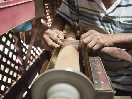 Hands of carpenter turning wood on lathe