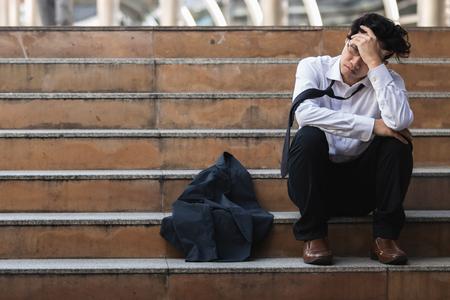 Arbeitsloser betonter junger asiatischer Geschäftsmann im Anzug, der Gesicht mit den Händen bedeckt Ausfall- und Entlassungskonzept.