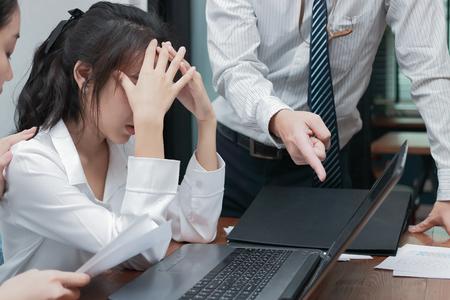 Depressa e stressata giovane donna d'affari asiatica che copre il viso sofferente del capo della mano in ufficio.