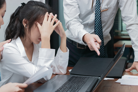 Depressive betonte junge asiatische Geschäftsfrau, die den Chef der leidenden Hand im Büro bedeckt.