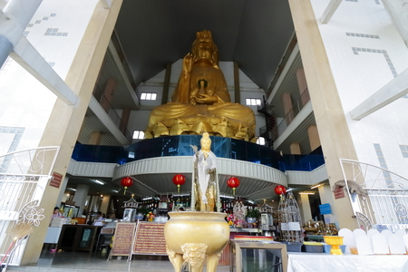 Ratchaburi , Thailand - March 10 , 2018 : Wide angle shot of the large golden statue of Guan Im at Nong Hoi temple