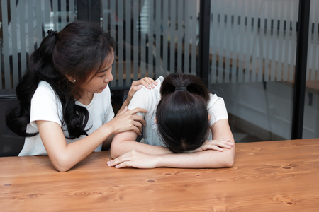 Asian woman comforting her depressed friend in living room.