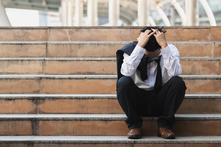 Upset stressed young Asian business man in suit with hands on head sitting on stairs. Unemployment and layoff concept.