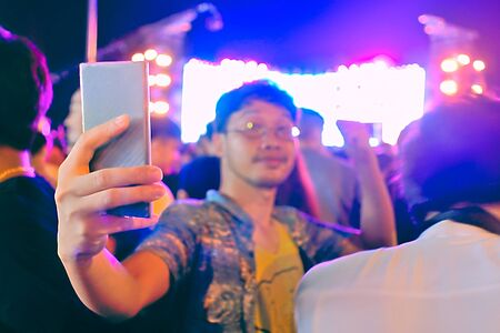 Hands of tourist taking picture of selfie in music concert festival.