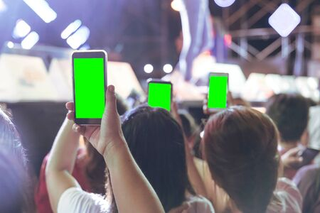 Hands of audience crowd people taking photo with mobile smart phone with green screen in party concert. Stock fotó