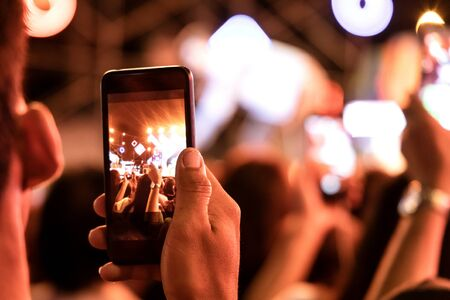 Hands of audience crowd people taking photo with mobile smart phone  in party concert.