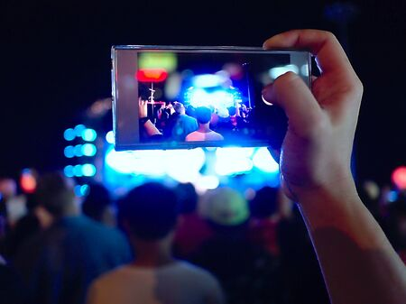 Hands of unidentified taking a photo with mobile smart phone of concert stage. Фото со стока