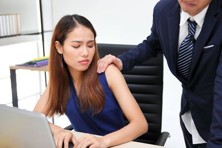 Man boss touching woman shoulder in workplace of office. Sexual harassment in office
