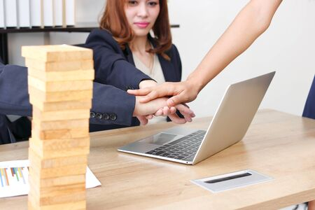 Young business partner joined hand together to greeting complete dealing in office. Success and teamwork concept. Stock Photo