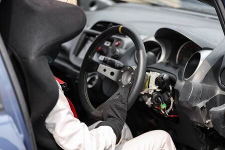 Car racer wearing protective leather and helmet holding a steering wheel Stock Photo
