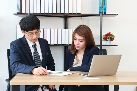 Young confident business colleagues analyzing documents and working together. Hardworking in office. 스톡 콘텐츠