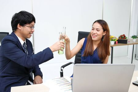 Cheerful young Asian business partners clinking bottle of wine in office. Successful and celebration concept.