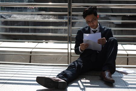 Frustrated stressed young Asian business man suffering from severe depression. Unemployment and layoff concept.