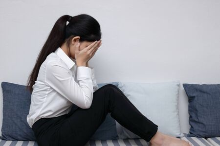 Frustrated upset young Asian woman  sitting in living room.