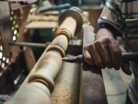 Hands of carpenter turning wood on lathe machine in carpentry workshop