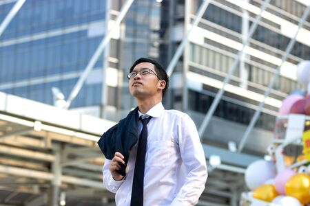 Confident young Asian business man in suit standing and looking at far away at outside office.