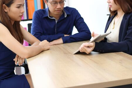 Young couple consulting with financial advisor in office.