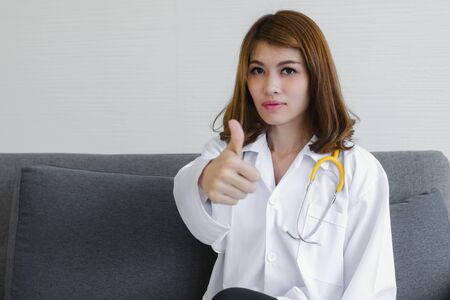 Portrait of medicine young Asian female doctor showing the gesture of thumps up at hospital office. 写真素材