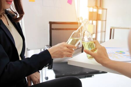 Success young Asian business partners clinking bottle of wine in office with sunshine effect. Successful and celebration concept. 写真素材