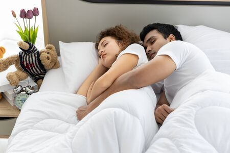 Romantic lovely couple in duvet lying on the bed in bedroom