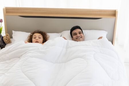 Lovely couple in duvet lying on the bed in bedroom