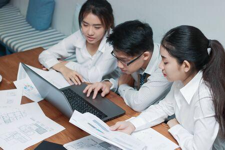 Concept d'entreprise de travail d'équipe. Groupe de personnes asiatiques travaillant avec un ordinateur portable ensemble dans un bureau moderne. Mise au point sélective et faible profondeur de champ.