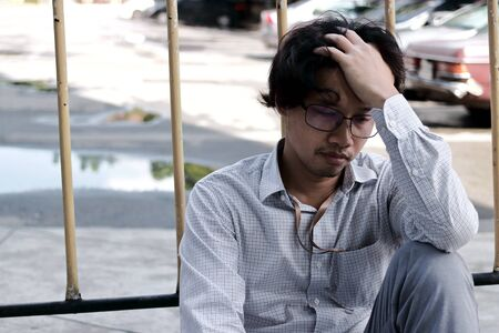 Tired and worried young Asian man suffering from severe depression
