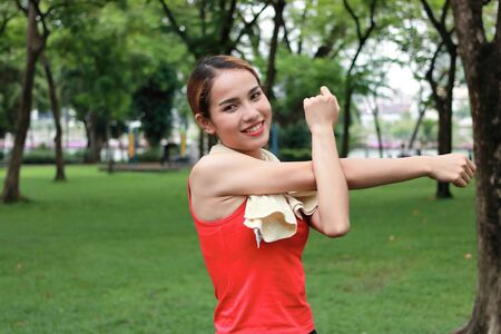 Healthy young Asian woman stretching her hands before run in park in morning. Workout and exercise concept.