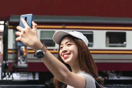 Cheerful young Asian woman traveler with backpack taking a photo or selfie in train station. Travel lifestyle concept.