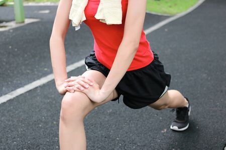 Healthy Asian woman stretching her legs before run in park. Fitness and exercise concept.