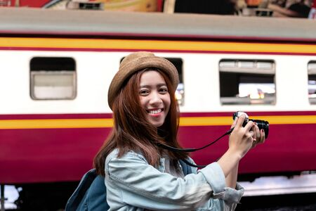 Smiling young Asian backpacker female holding digital camera at train station. Travel lifestyle concept.