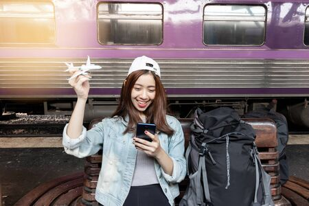 Cheerful young Asian woman traveler with model train sitting on bench waiting for arriving train at station.