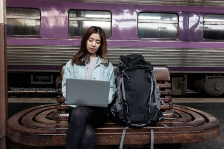 Attractive young Asian lady backpacker using computer laptop for plan to trip. Travel lifestyle concept.