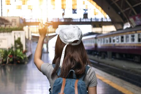 Back view of young Asian tourist girl holding model airplane at train station. Travel lifestyle concept. 写真素材