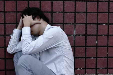 Side view of unhappy depressed young Asian man sitting and feeling bad