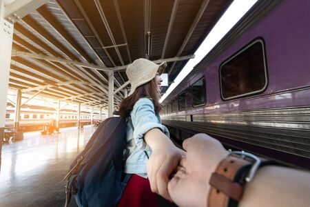 In love young Asian woman holding boyfriend hands follow her at train station. Romantic and travel in summer vacation concept. 写真素材