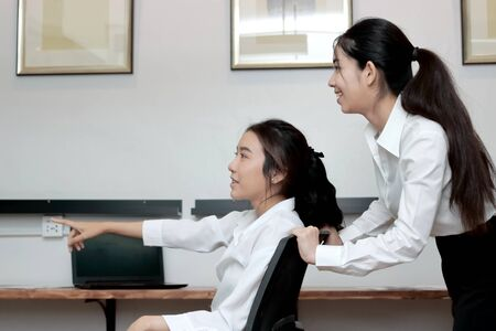 Two playful young Asian business woman playing together with chair in office.