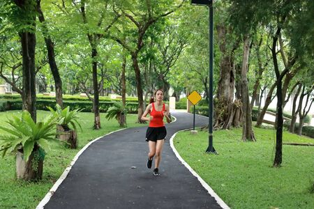 Relaxed smiling Asian fitness runner woman listening music and running workout in natural park.