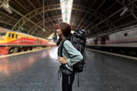 Confident young Asian backpacker woman looking new challenges at train station. Summer travel vacations lifestyles