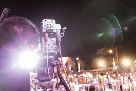 Professional digital camera recording video in music concert festival