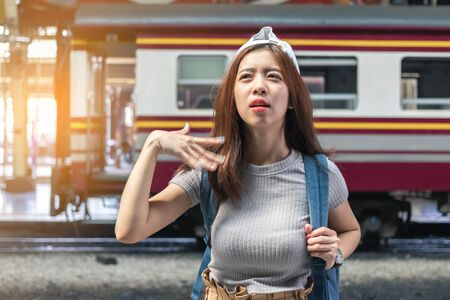 Tired young Asian female feeling so hot at train station. Travel lifestyle concept.