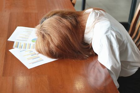 Soft focus of tired overworked young business woman bend down head on charts in office.