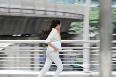 Abstract blurred motion of young Asian business woman running to work. 写真素材