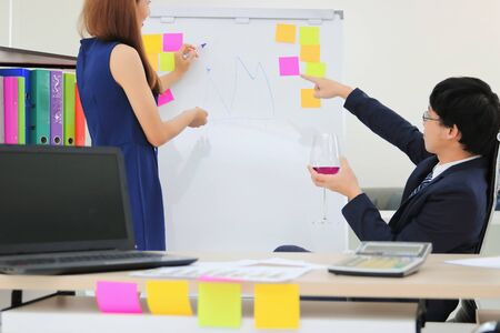 Executive boss holding a glass of wine with confident young Asian business woman explaining strategies on flip chart in boardroom