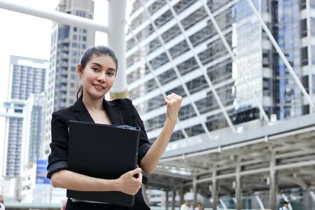 Successful young Asian business woman with binder raising arms.