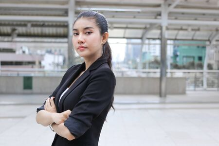 Confident young Asian business woman crossing ones arms at outside office. 写真素材