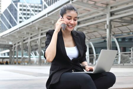Attractive young Asian business woman working with laptop and mobile smart phone at outside office.