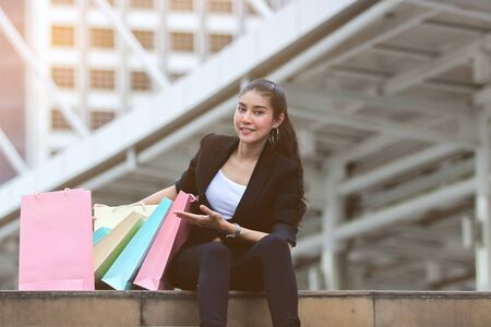 Cheerful young Asian woman with colorful shopping bag in modern city.