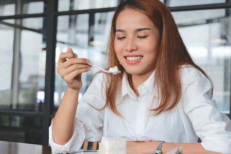 Cheerful Asian woman eating a peace of coconut cream cake in living room