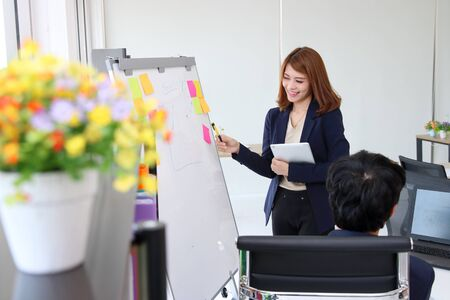Attractive young Asian business woman explaining strategies on flip chart to executive in boardroom 写真素材